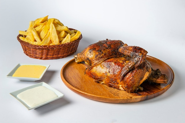 Delicious whole grilled chicken with french fries and creams on wooden plate.