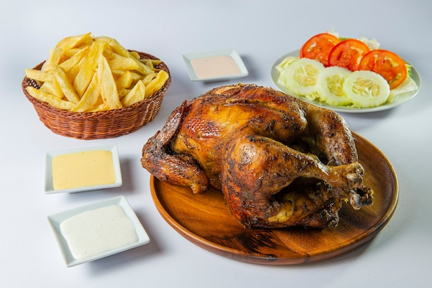 Delicious whole grilled chicken with french fries, salad and creams on wooden plate.