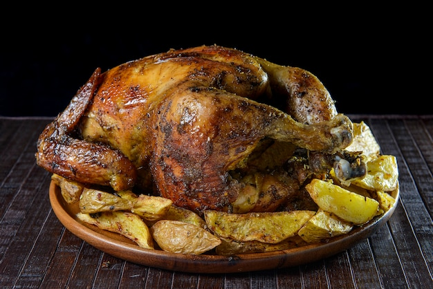 Delicious whole grilled chicken with potato wedges on wooden plate. peruvian food