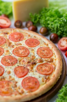 Delicious whole pizza margherita served with vegetables and cheese