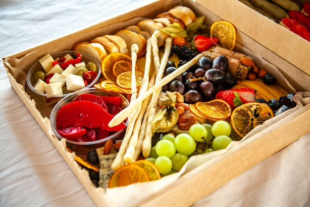 Delicious wine snacks in a cardboard box for a buffet for a party: cheeses, sausages, cold cuts, fruit, baguette, grissini