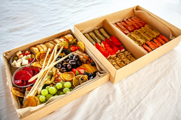 파티를 위한 뷔페를 위한 골판지 상자에 담긴 맛있는 와인 스낵: 치즈, 소시지, 콜드 컷, 과일, 바게트, 그리시니