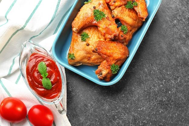 台所のテーブルの上の鶏肉のソースとおいしい翼