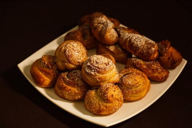 茶色のテーブルクロスの白い皿に粉砂糖をまぶした、無愛想なロールパンで美味しい