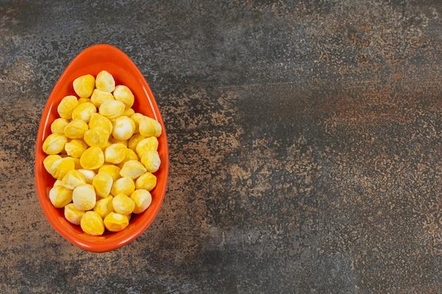 오렌지 그릇에 맛있는 노란색 사탕.