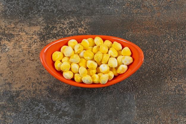 Caramelle gialle deliziose in ciotola arancione.