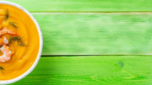 Delicious yellow pumpkin cream soup with shrimp on bright green