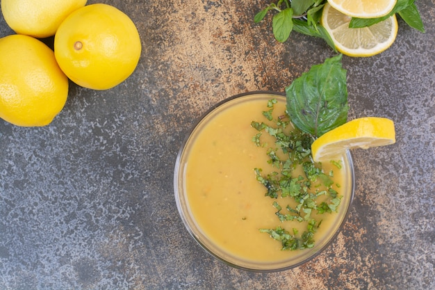 Вкусный желтый суп с зеленью и лимонами на стеклянной тарелке