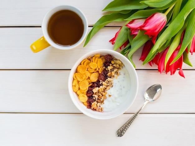 白い木製のテーブルにコーンフレーク、ナッツ、ジャムが入ったおいしいヨーグルトボウル。健康的で有機的な栄養の概念。お茶と朝食のチューリップ。上面図、コピースペース