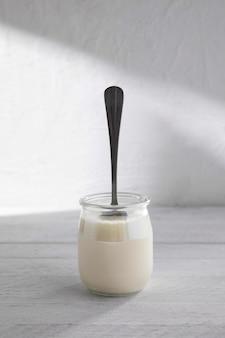 Вкусный йогурт в стакане с ложкой