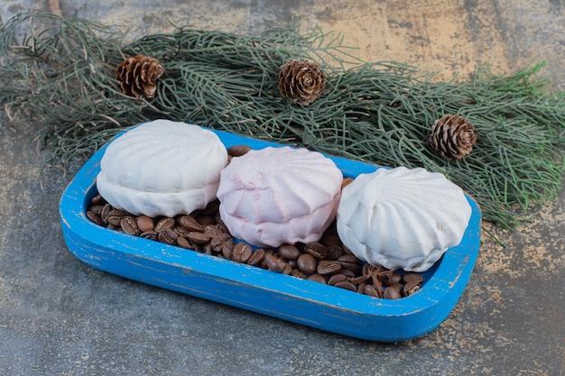 Вкусный зефир с кофейными зернами в голубой тарелке. фото высокого качества