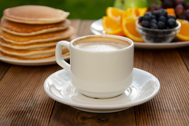 Deliciouse homemade american pancakes with cup of coffee and fruits.