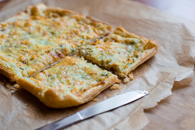 Deliciously simple cheese tart with green peas and eggs on parchment paper. summer tart. top view
