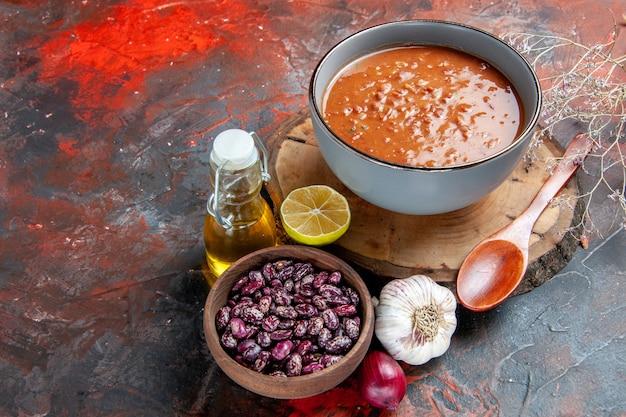 Delicioussoup на ужин с ложкой и лимоном на деревянном подносе, фасоль, чеснок, лук и бутылка масла на столе смешанных цветов
