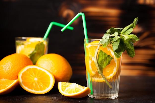 스튜디오 사진의 나무 배경에 있는 맛있는 건강한 오렌지에이드