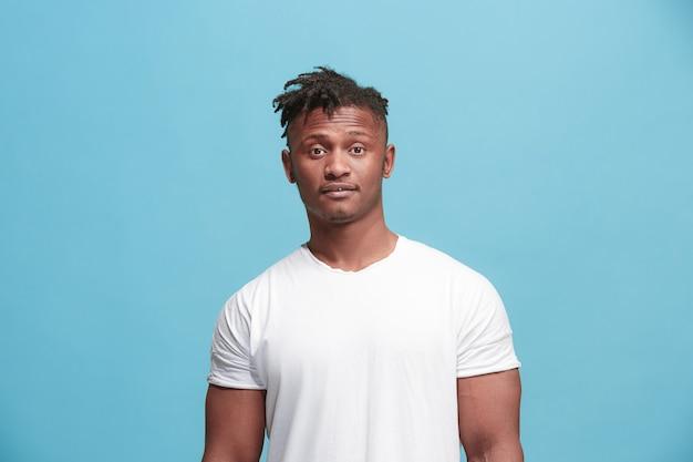 喜び。青いスタジオ背景に分離されたアフリカ系アメリカ人男性のハーフレングスのフロントの肖像画。若い、感情的な、笑みを浮かべて、立っている驚いた男。人間の感情、表情のコンセプト。流行色