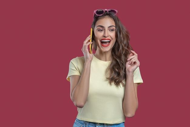喜び、コミュニケーション。喜びと話している耳の近くに立っているスマートフォンで口を開けて若い感情的な女性