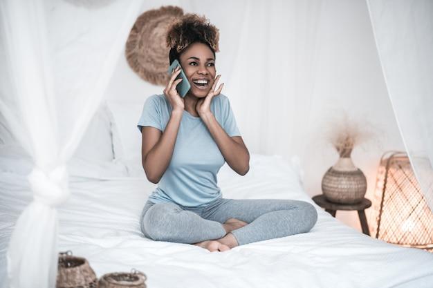 喜び、感情。ベッドに座っている彼女の耳の近くにスマートフォンを持つ家庭服を着た熱狂的な感情的な浅黒い肌の若い女性