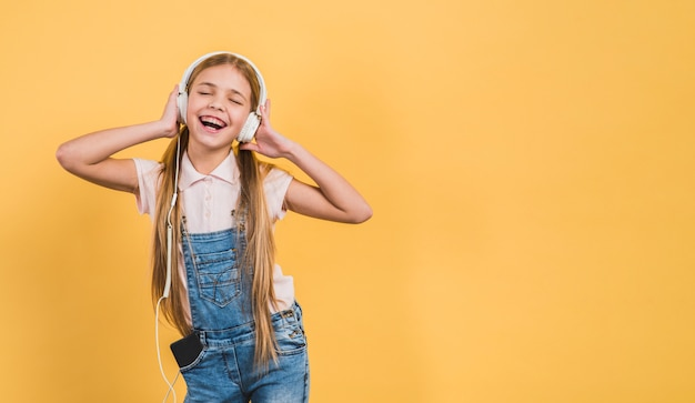 Delight girl enjoying listening the music on headphone against yellow backdrop