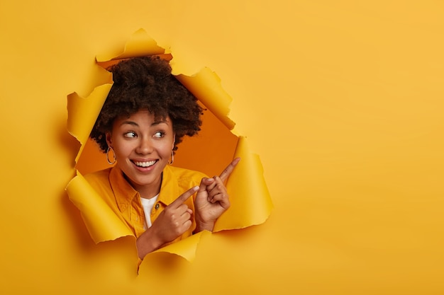 Delighted adorable woman with afro hairstyle points away with both fore fingers, smiles gladfully and shows white teeth, demonstrates copy space for your advertisement