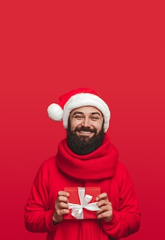 Delighted adult bearded male in santa hat and scarf holding small gift