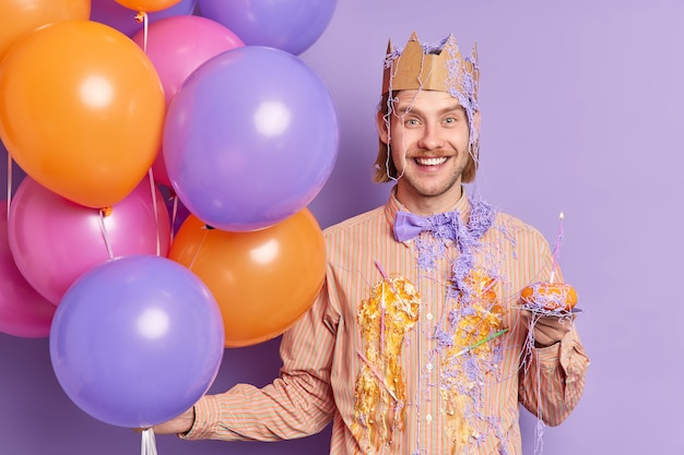 Delighted adult man dirty with cake cream holds small cupcake with candle has fun at bachelor party wears paper crown on head holds colorful inflated balloons isolated over purple wall