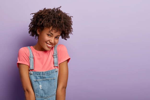 Delighted african american woman has cheerful shy face expression, expresses positive emotions, wears pink t shirt and denim sarafan, models over purple wall, copy space aside