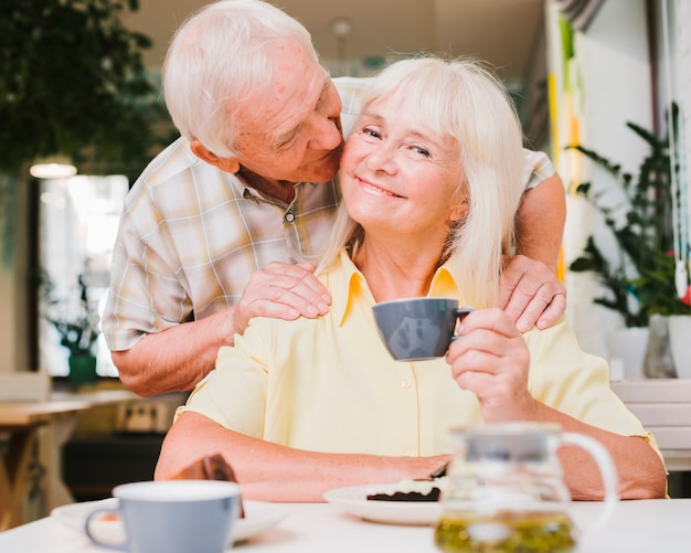 Delighted aged couple sitting in cafe and kissing