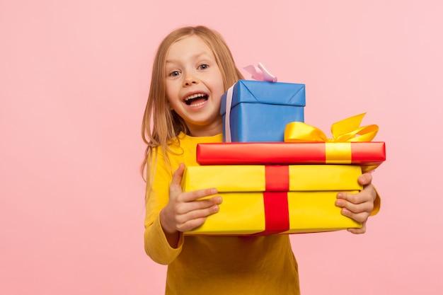 많은 선물 상자를 껴안고 놀란 어린 소녀가 놀라움과 어린애 같은 행복으로 카메라를 바라보며 많은 생일 선물에 충격을 받았습니다. 실내 스튜디오 촬영, 분홍색 배경
