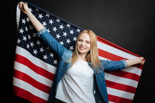 Довольная, веселая молодая женщина веселится и выражает радость, держа национальный флаг и стоя изолированно в черной стене