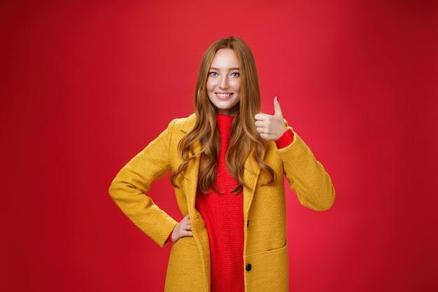 喜んで満足している女性の赤毛の顧客は、赤い背景の上に立っている新しい黄色のコートの素晴らしい品質に満足し、広く幸せに笑って、親指を立てて承認しました。