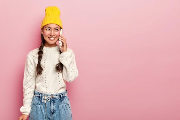 기뻐하는 아시아 여성이 스마트 폰을 통해 대화하고, 유쾌한 대화를 나누고, 친구에게 전화를 걸고, 따뜻한 흰색 점퍼와 청바지를 입고, 미소를 지으며 옆으로 보이며, 분홍색 벽 위에 포즈를 취합니다.