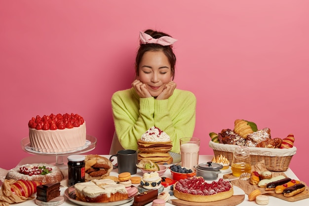 Delighted asian woman wears headband and green jumper, holds chin, has good appetite, eats sweet food, fruit cakes, comes on birthday party, isolated on pink wall