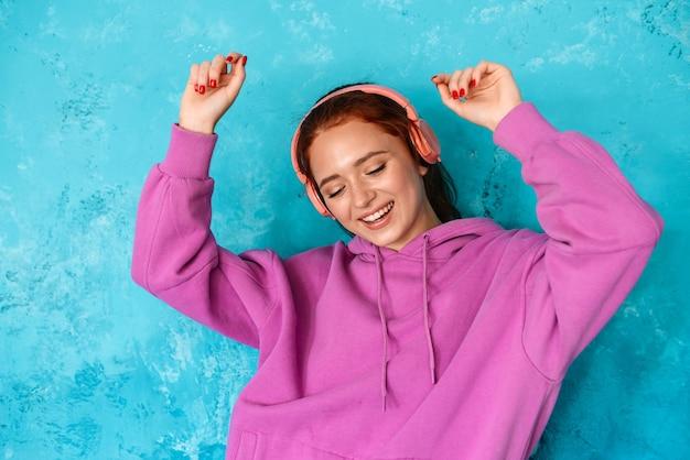 Восхищенная привлекательная женщина в наушниках слушает музыку и танцует изолированно над синей стеной в помещении