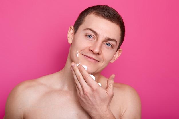 喜んで魅力的な若い男が彼の顔からシェービングジェルを拭く、満足そうに見えます。裸のアスレチックブルーの目をしたモデルは、片方の手で顔に触れ、別の方向を向いています。広告用のスペースをコピーします。