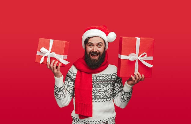 Delighted bearded hipster in scarf and santa hat