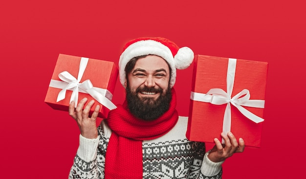 Delighted bearded man in santa hat smiling and showing wrapped presents