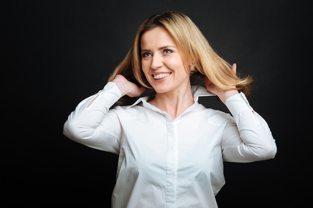 Delighted beautiful mature woman smiling and expressing positivity while flirting and standing isolated in black wall