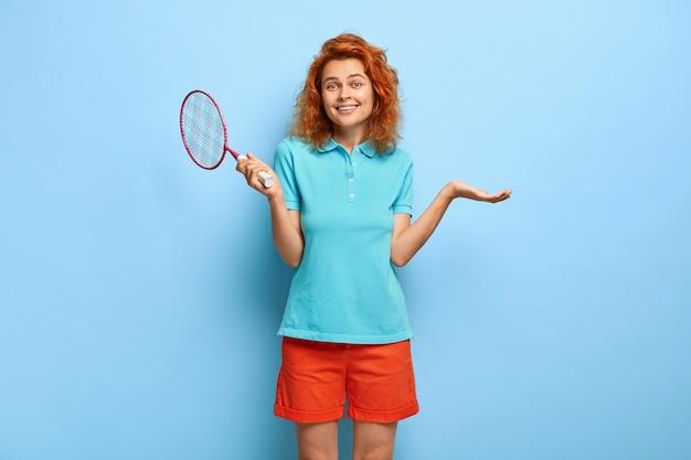 バドミントンラケットで喜んで美しい赤毛の女性