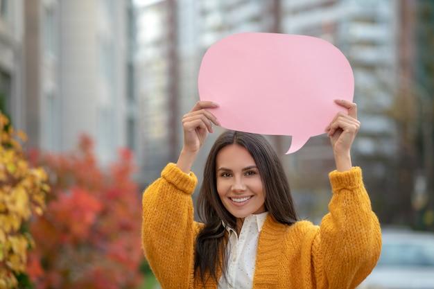 彼女の上にピンクの看板を持って笑って喜んで美しい女性