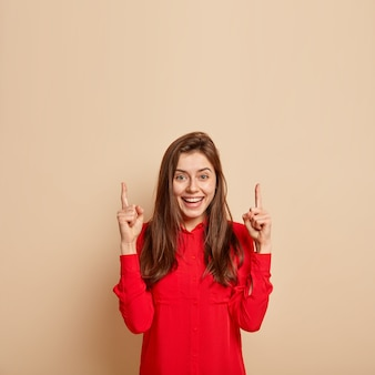 Delighted beautiful young woman points upwards, looks impressed and fascinated, dressed in red fashionable shirt, demonstrates item against beige wall, shows blank space for your promotion