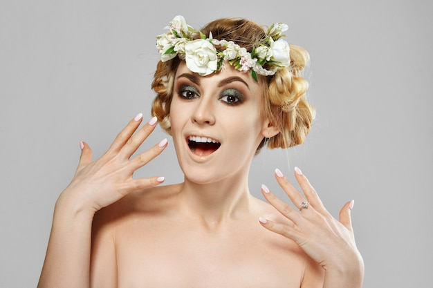 Delighted beauty model girl with flowers in her hair. perfect creative make up and floral art hairstyle.