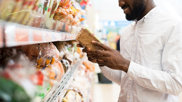 Delighted black male choosing bread at grocery store