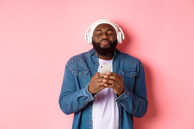 Felice uomo nero che si gode musica fantastica, ascolta canzoni in cuffia e tiene in mano lo smartphone, sembra estatico, in piedi su sfondo rosa