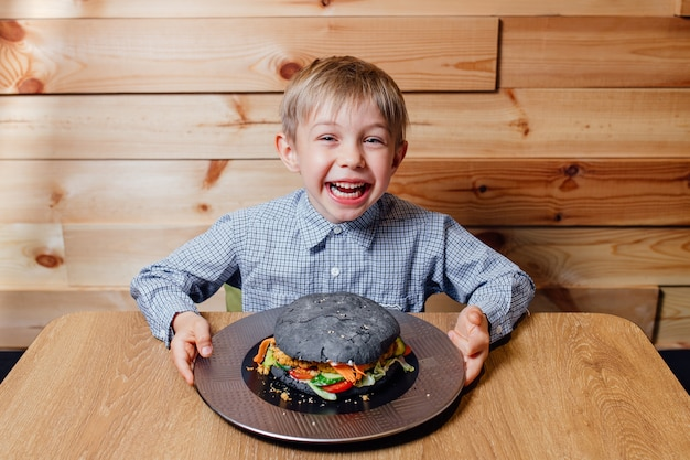 巨大なハンバーガーで喜んでいる少年