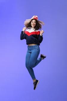 温かいビーニーで巻き毛の気楽で幸せな若い女性が楽しくジャンプして喜んで...