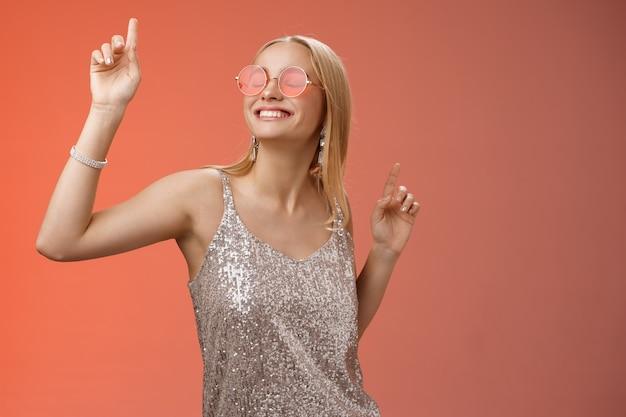 Восхищенная беззаботная привлекательная стильная тысячелетняя белокурая женщина празднует вечеринки с удовольствием носит солнцезащитные очки в модном серебряном платье, танцует с закрытыми глазами, широкая улыбка, машет руками, красный фон.