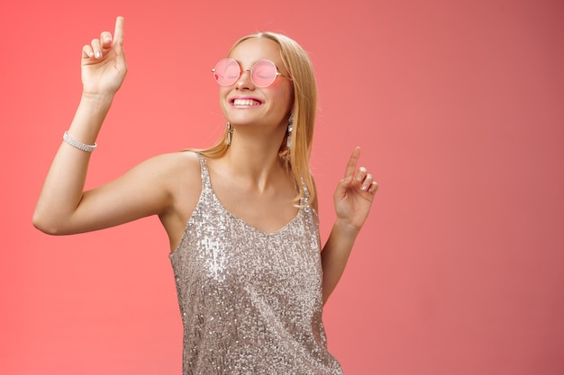 Felice spensierata attraente ed elegante donna bionda millenaria che celebra la festa divertendosi indossando occhiali da sole alla moda vestito d'argento ballando gli occhi chiusi ampio sorriso agitando le mani in alto, sfondo rosso.