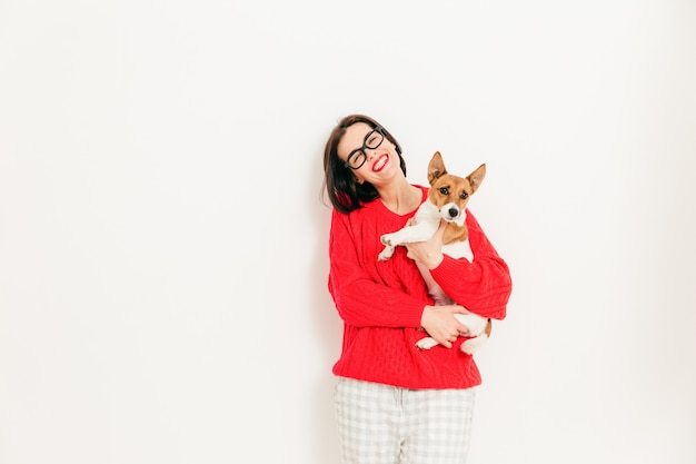 Delighted caucasian female carries jack russell terrier dog, wears spectacles and red sweater, enjoys spare time with favourite pet