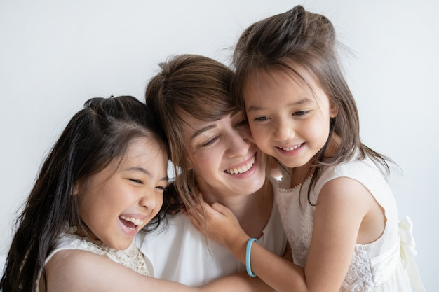 Delighted caucasian mother and daughters laughing and hugging